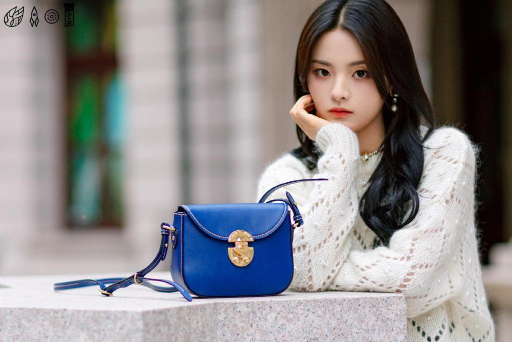 杨超越街拍:白色针织衫黑色短裙蓝色挎包